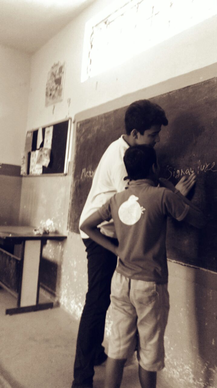 Jayansh working with a student at a school during his internship